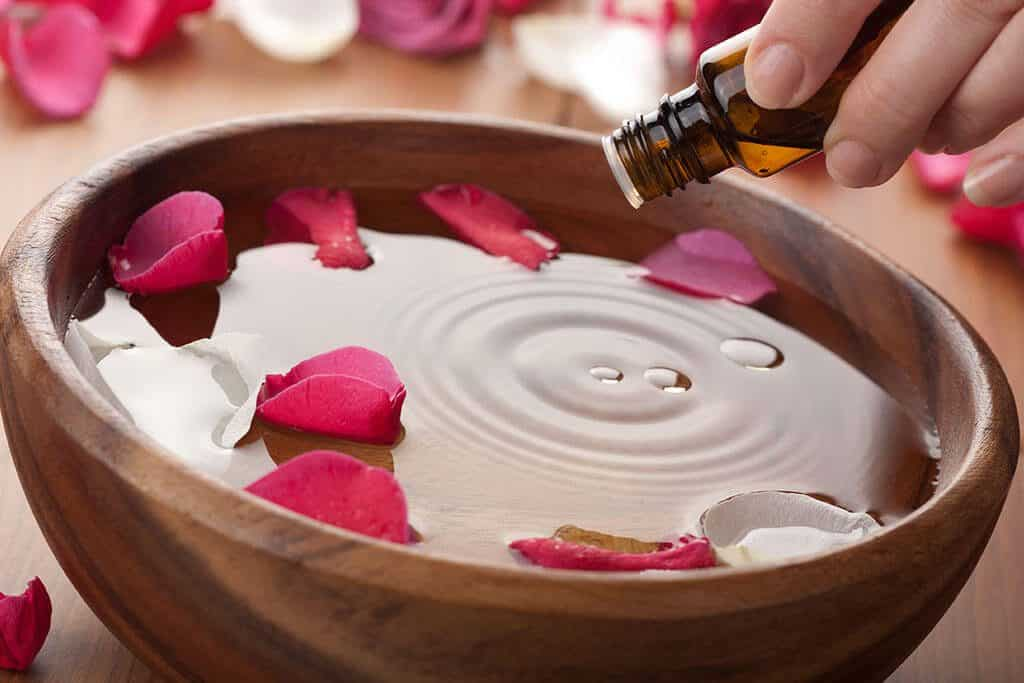 Drop of essential oil being poured into a bowl with water